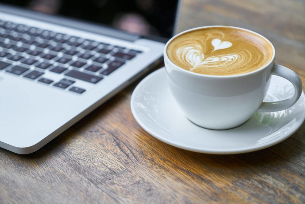 picture of latte coffee art and a laptop computer