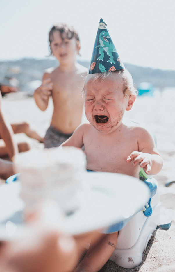 Toddler in a birthday hat cries as a small cake is brought to him on the beach